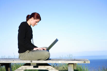 Young woman working on a laptop on a rustic environment outdoors.
